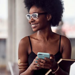 Cheerful african american woman holding smartphone and notepad