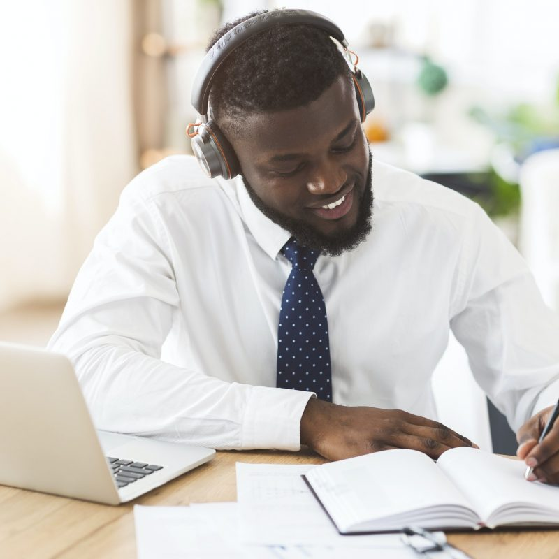 Creative businessman listening to music at workplace, planning future